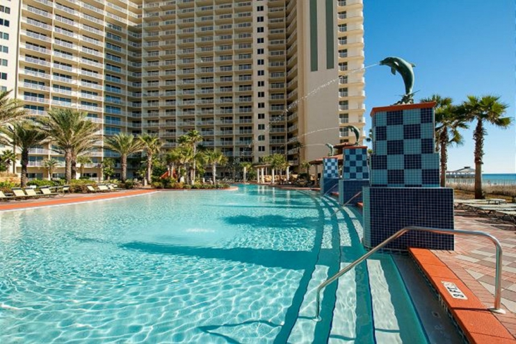 Expansive pool area with views of Gulf and plenty of lounge chairs.