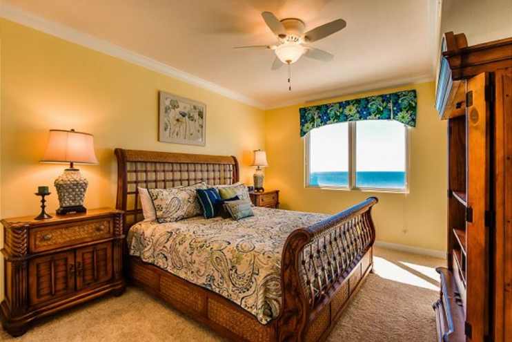 Master bedroom with King sized bed, luxurious blanket and plenty of pillows.